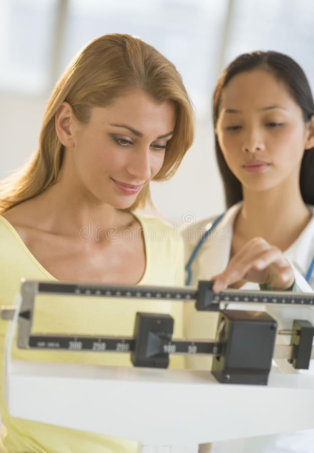Doctor Weighing Woman On Balance Weight Scale. Mid adult female doctor weighing women on balance weight scale in clinic stock image