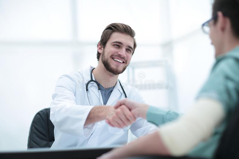 Doctor welcoming a patient in his studio royalty free stock photos