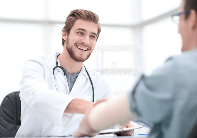 Doctor welcoming a patient in his studio stock image