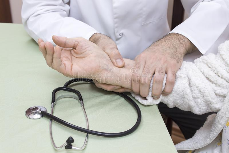 Doctor in a white coat examines the pulse on the wrist of an old woman in a white bathrobe. The stethoscope is on the table stock images