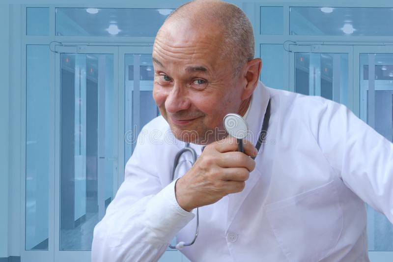 Doctor in a white coat with a phonendoscope in his hand looks slyly, squinting, against the blue background of the clinic stock image