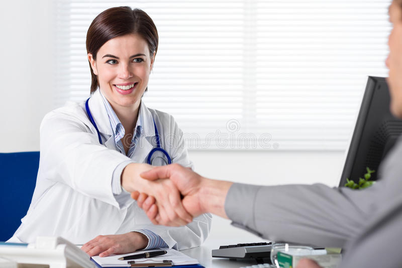 Doctor in white coat shake hand stock photography