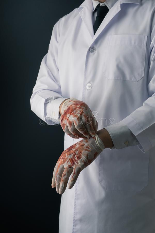 A doctor in white coat wearing bloody latex gloves stock image