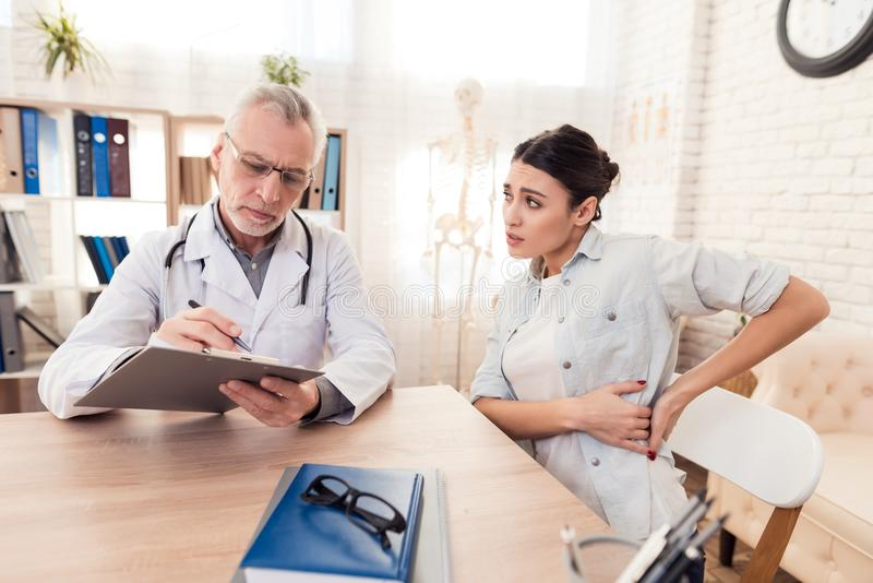 Doctor with stethoscope and female patient in office. Patient`s side hurts. Doctor in white gown with stethoscope and female patient in office. Patient`s side stock image