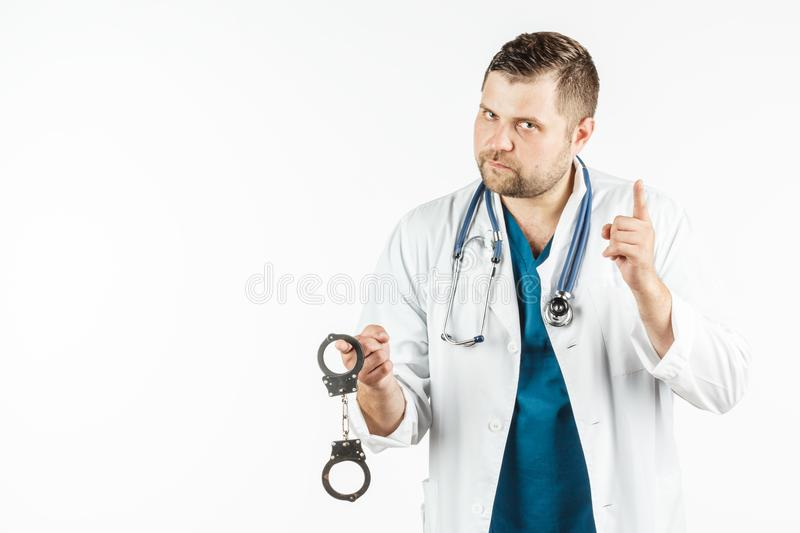 A doctor in a white lab coat with a stethoscope holds the handcuffs in his hand. stock photos