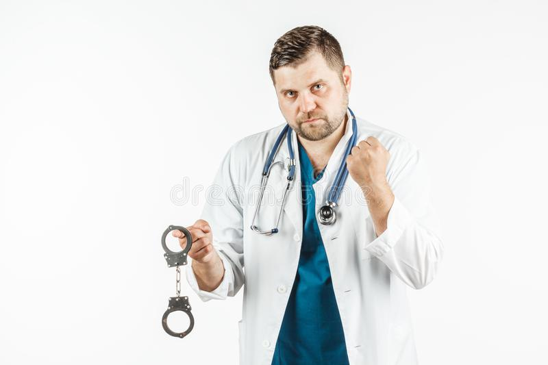 A doctor in a white lab coat with a stethoscope holds the handcuffs in his hand. royalty free stock photos