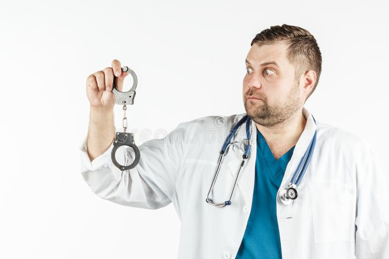 A doctor in a white lab coat with a stethoscope holds the handcuffs in his hand. royalty free stock photography