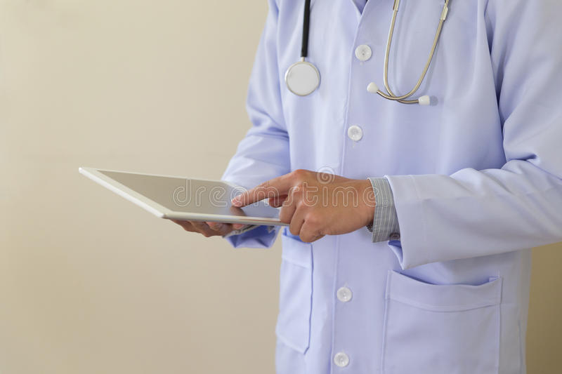doctor in white lab coat using his tablet computer at work stock images