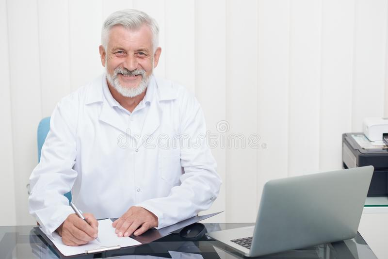 Doctor in whitecoat looking at camera, noting prescriptions. stock photo