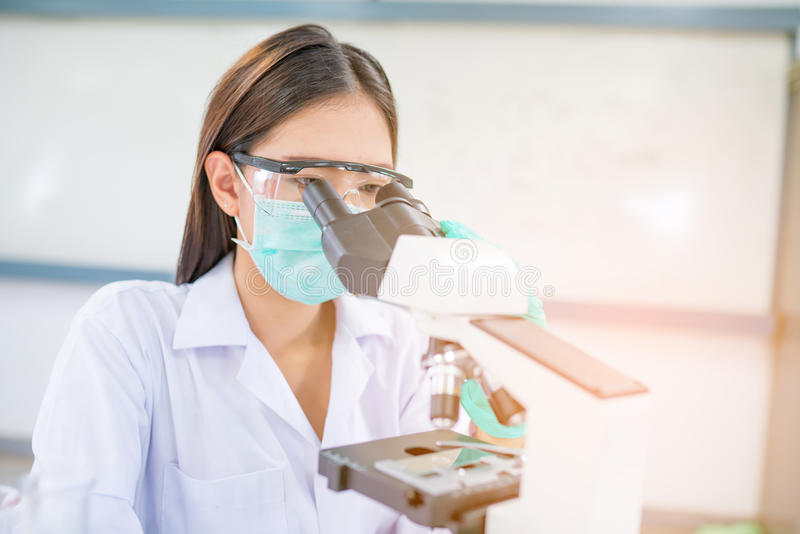 Doctor woman or chemist working with microscope. In laboratory room royalty free stock images