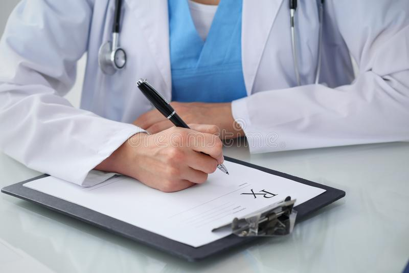 Doctor woman filling up prescription, close-up of hands. Physician at work. Medicine and healthcare concept.  royalty free stock photo