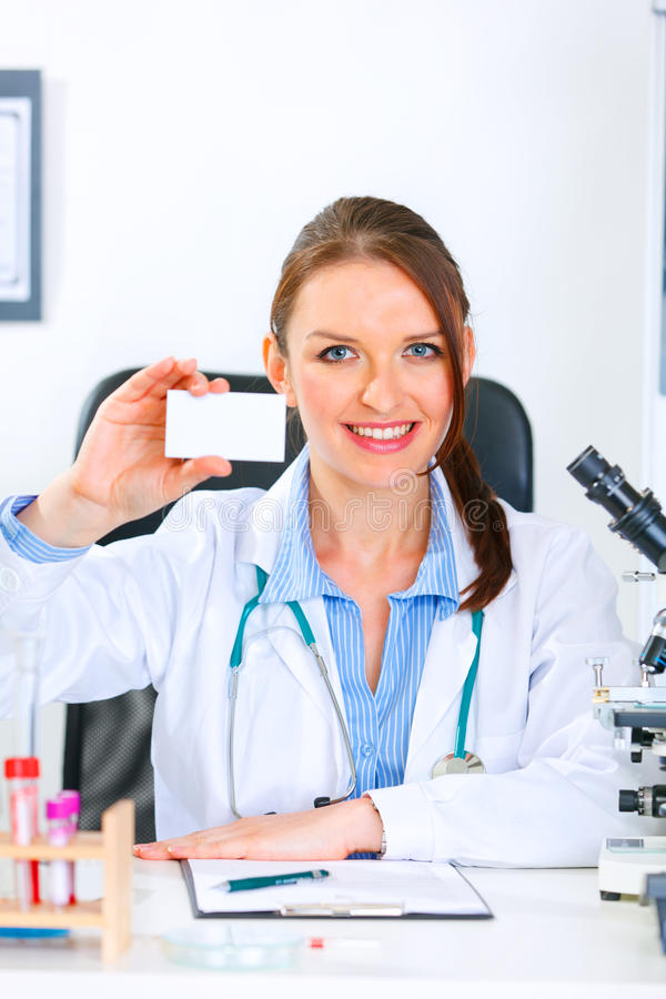 Doctor woman holding blank business card. Smiling medical doctor woman sitting at office table and holding blank business card stock photography