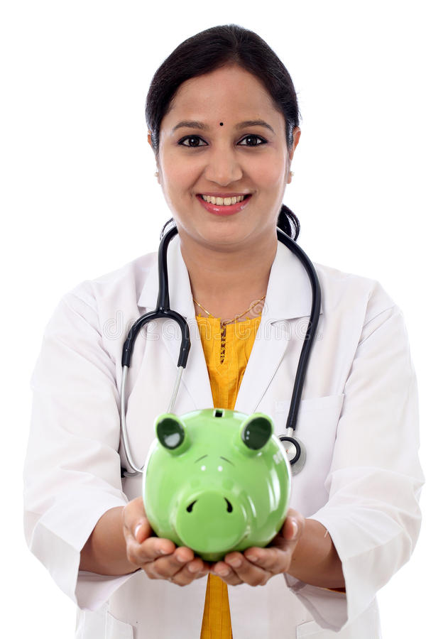 Doctor woman holding a piggy bank. Against white background royalty free stock image