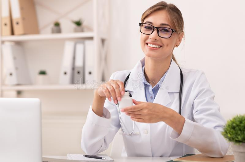 Smiling Doctor Woman Holding Prescribed Medication Jar Sitting In Office royalty free stock image