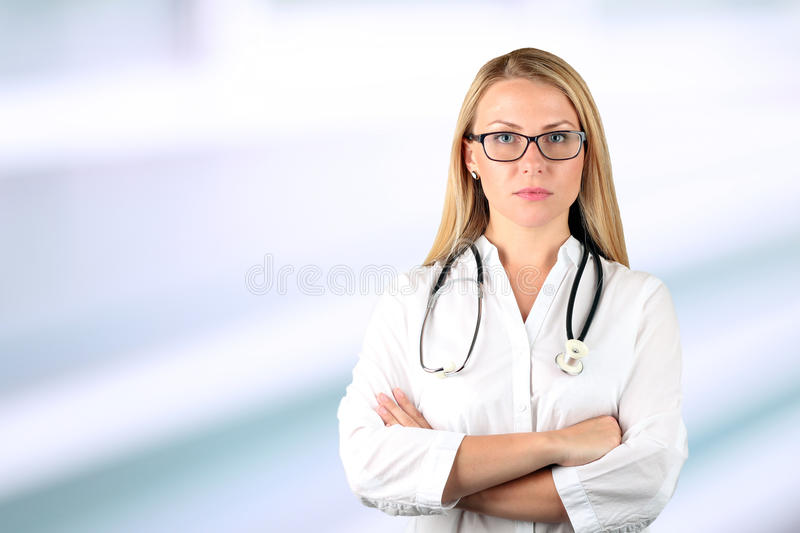 Doctor woman looking at camera. Blue background stock photos