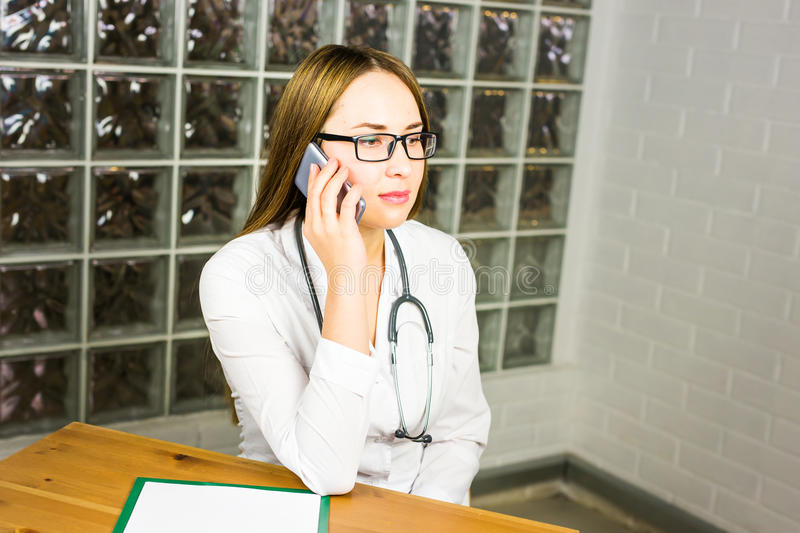Doctor woman in medical office smiling and talking on the phone.  stock images
