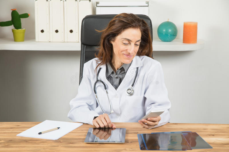 Doctor woman reading mobile phone in office. Brown hair doctor woman, with white gown and stethoscope, sitting smiling and reading or typing in mobile phone royalty free stock images