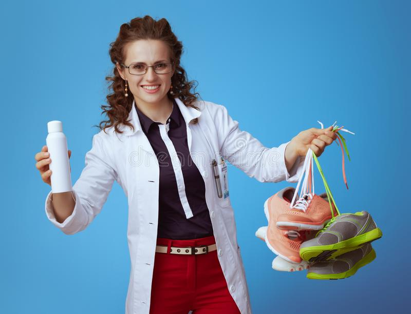 Doctor woman showing fit sneakers and shoe deodorizer spray. Happy modern medical practitioner woman in bue shirt, red pants and white medical robe showing royalty free stock photo