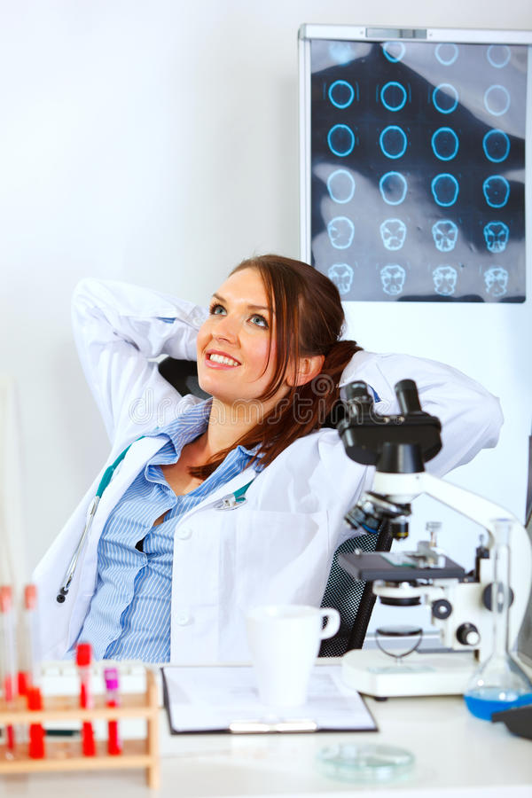 Download Doctor Woman Sitting At Office Table And Relaxing Stock Image - Image: 21608897