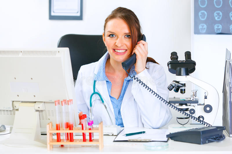 Doctor woman sitting at table and talking on phone. Smiling medical doctor woman sitting at office table and talking on phone royalty free stock photography