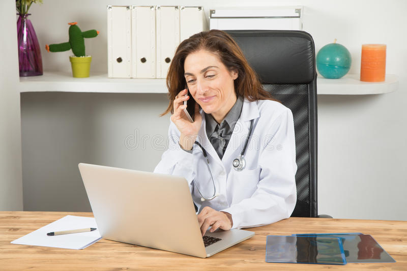 Doctor woman talking on phone and typing laptop. Brown hair doctor woman, with white gown and stethoscope, sitting in wooden table smiling, talking on the phone royalty free stock photos
