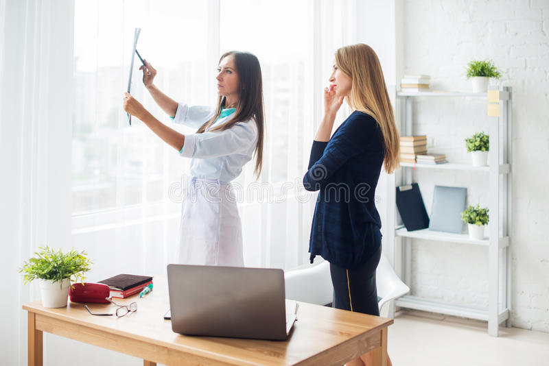 Doctor woman with white labcoat looking at x-ray. Doctor women with white labcoat looking at x-ray radiographic results ct scan mri in hospital clinic royalty free stock image