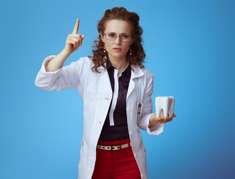 Doctor woman with white tooth warning with rises finger on blue. Modern doctor woman in bue shirt, red pants and white medical robe with white tooth warning with stock photos