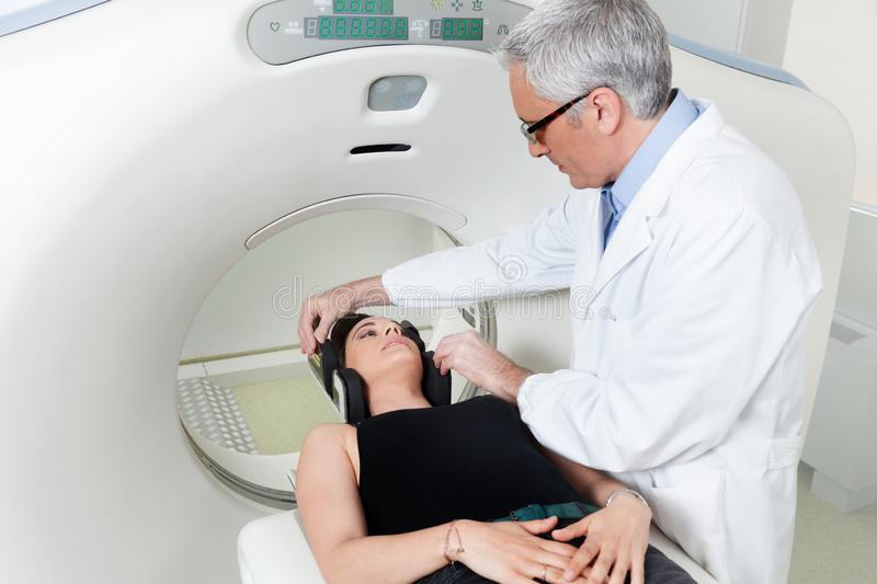 Doctor with woman who is doing a CT scanner. Doctor in white coat is preparing patient for magnetic resonance imaging machine MRI computed tomography at hospital royalty free stock photography