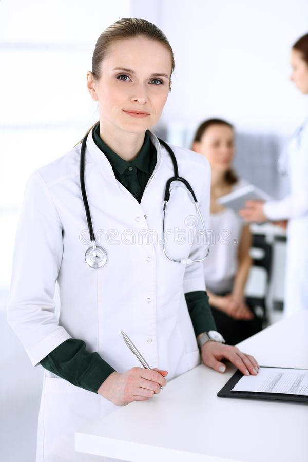 Doctor woman at work with patient and colleague at background. Physician filling up medical documents or prescription stock photography
