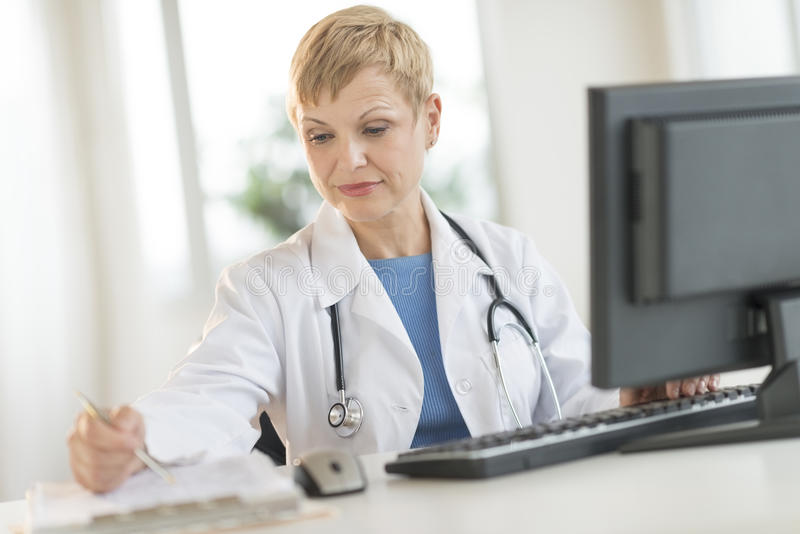 Doctor Working At Computer Desk In Clinic Royalty Free Stock Images