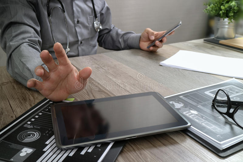 Doctor working with digital tablet computer with smart phone in. Medical workspace office and video conference as concept stock images