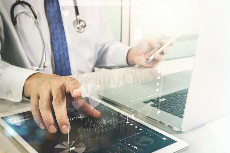 Doctor working with digital tablet and laptop computer with smart phone in medical workspace office and video conferance as. Concept royalty free stock photos