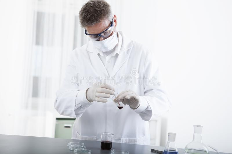 Doctor working with microscope and blood stock image
