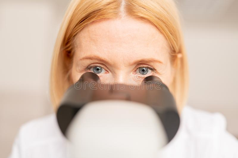 Doctor working with microscope. Close-up of concentrated blue-eyed lady doctor with blond hair working with microscope while analyzing sample royalty free stock photo