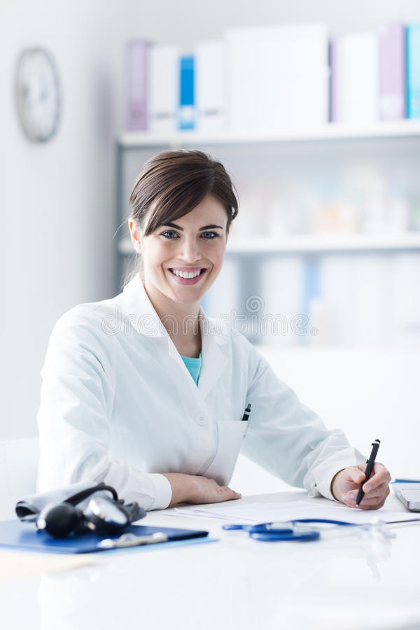 Doctor working at office desk stock photos