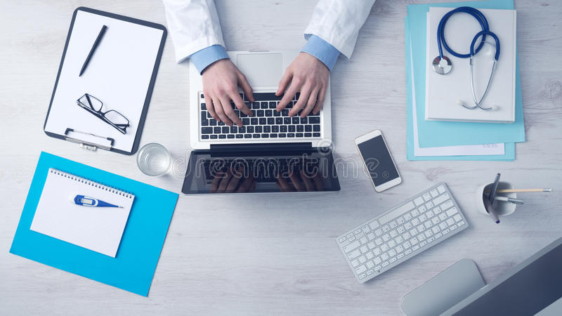Doctor working at office desk stock photography