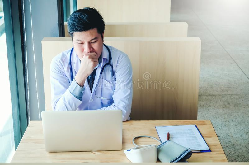 Doctor is working in office sitting, thinking about Disease problem of patient royalty free stock photos