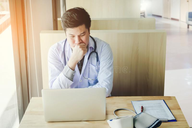 Doctor is working in office sitting, thinking about Disease prob stock photo