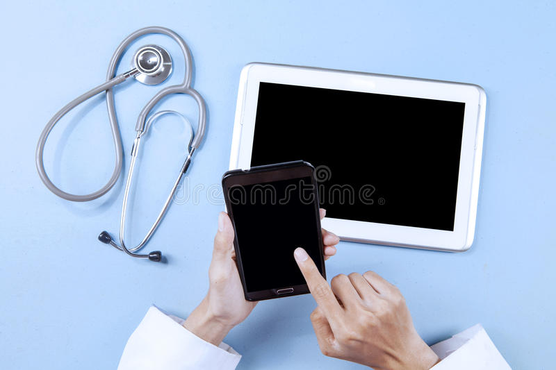 Doctor working with smartphone. And digital tablet while touching the screen royalty free stock images