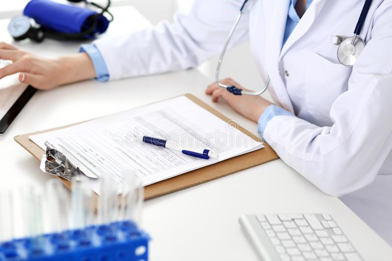Doctor working table. Woman physician using tablet computer while sitting in hospital office close-up. Healthcare royalty free stock images