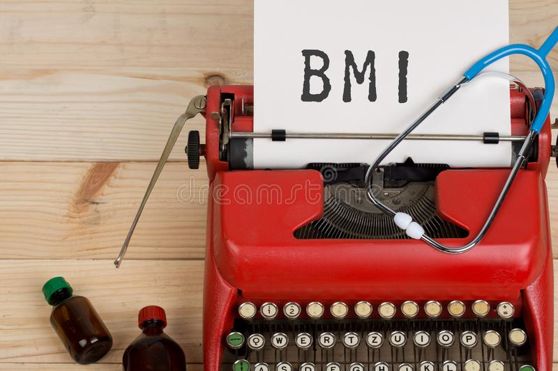 Doctor workplace with blue stethoscope, pills, red typewriter with text BMI Body mass index. Prescription medicine or medical diagnosis - doctor workplace with stock photography