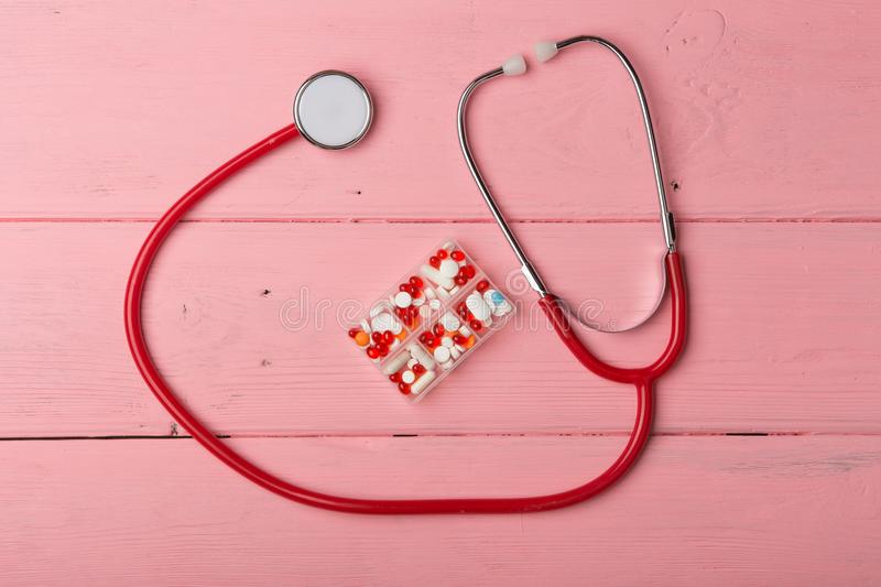 Doctor workplace. Medical, medicine red stethoscope and pills on pink wooden table. Medication prescription. stock image
