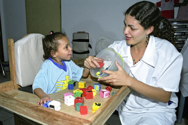 Doctor works with handicapped child, Brazil. Brazil, Pernambuco, city Gravata: a female psychiatrist is to test physical and cognitive abilities of a girl with a royalty free stock photography