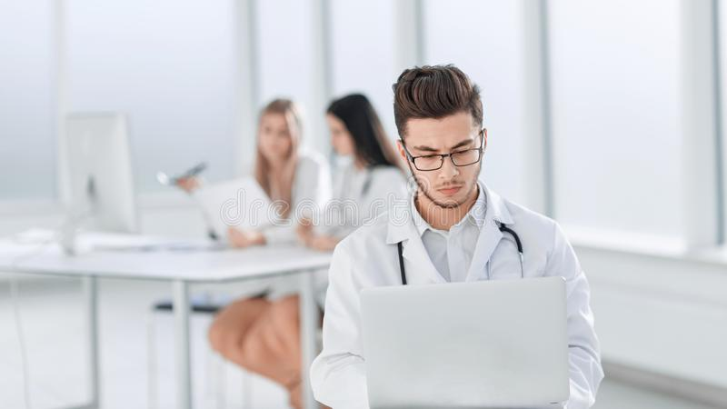 Doctor works on a laptop in the hospital room stock photography