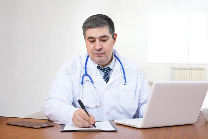 Beautiful female doctor. A doctor works in the office at a computer and writes in a workbook stock photos
