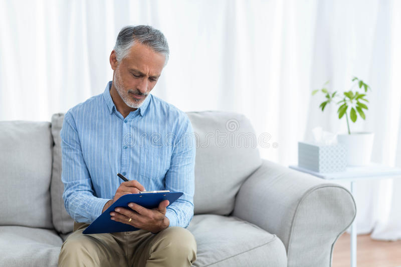 Doctor writing on clipboard royalty free stock photos