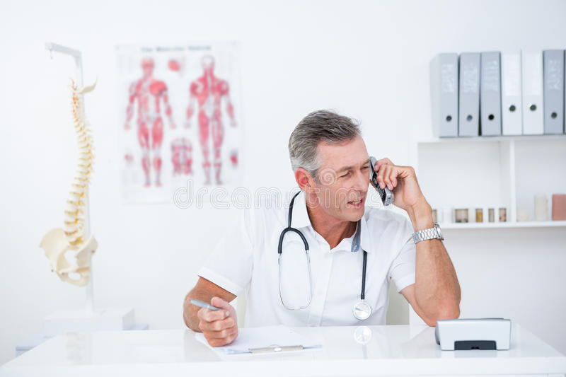 Doctor writing on clipboard and phoning stock images