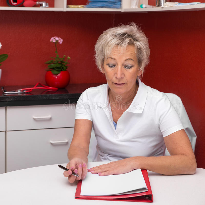 Doctor is writing a documentation. Female doctor is writing a documentation in her office, red background royalty free stock images