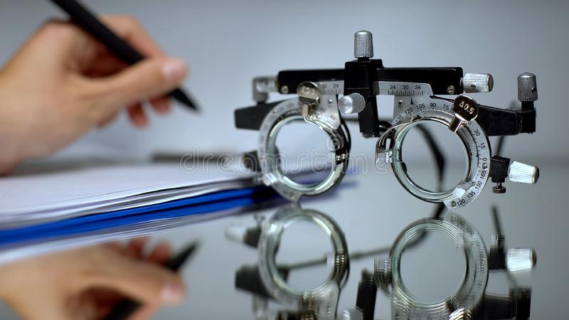 Doctor writing eyeglass prescription, vision check with optical trial frame royalty free stock images