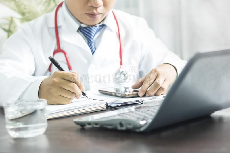 Doctor writing information to patient on medicine paper in clinic royalty free stock photography